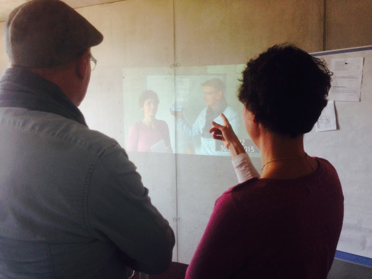 Ein Foto von Joachim und Nina, die auf eine Projektion von Joachim und Nina gucken.