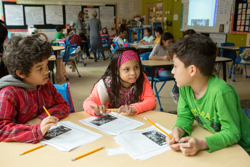 """Fourth graders work together to plan life for their """"colony"""" during a class activity focused on colonial America."""
