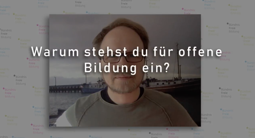 Jöran Muuß-Merholz vor einem Poster in einem Video vom Bündnis freie Bildung