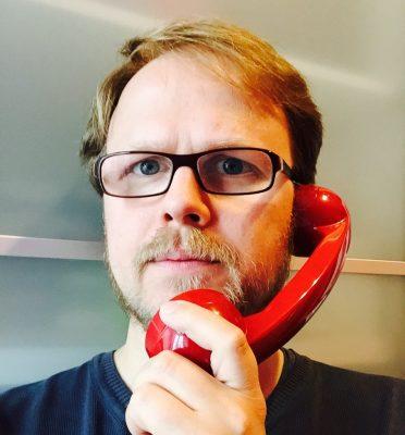 Jöran Muuß-Merholz mit einem roten Telefonhörer am Ohr