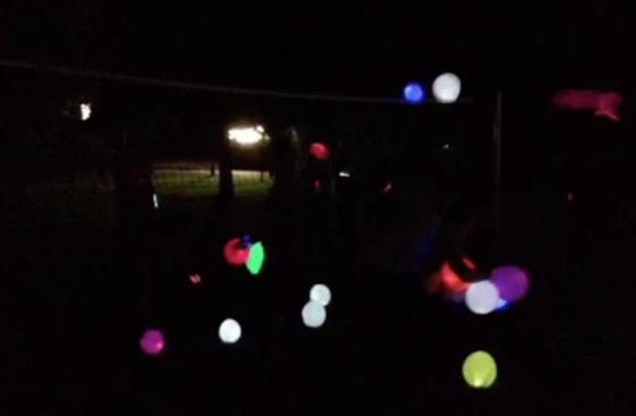 farbig leuchtende Luftballons vor dunklem Hintergrund