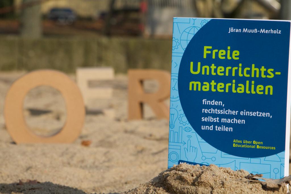 """Das Buch mit dem Titel """"Frei Unterrichtsmaterialien"""" (im Sand)"""
