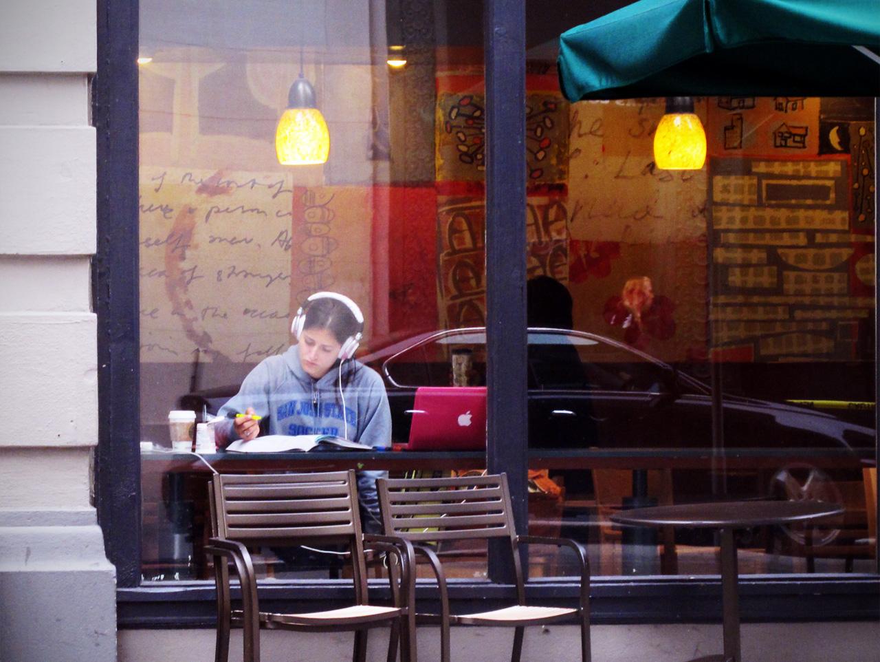 Frau mit Kopfhörer, Laptop und Papier hinter einem Starbucks-Schaufenster