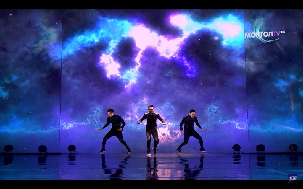 drei gleich aussehende Tänzer vor einem bunten Display