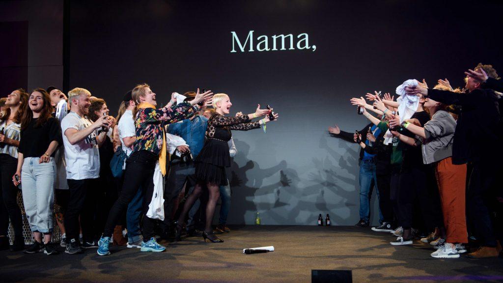 """Menschen singend und posierend auf einer Bühne, auf deren Hintergrund """"Mama"""" steht"""