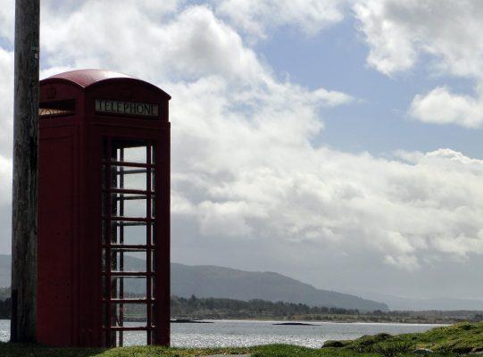Telefonzelle vor See und Himmel
